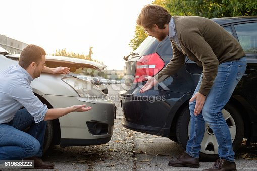 1047083324 istock photo Two men arguing after a car accident on the road 619633222