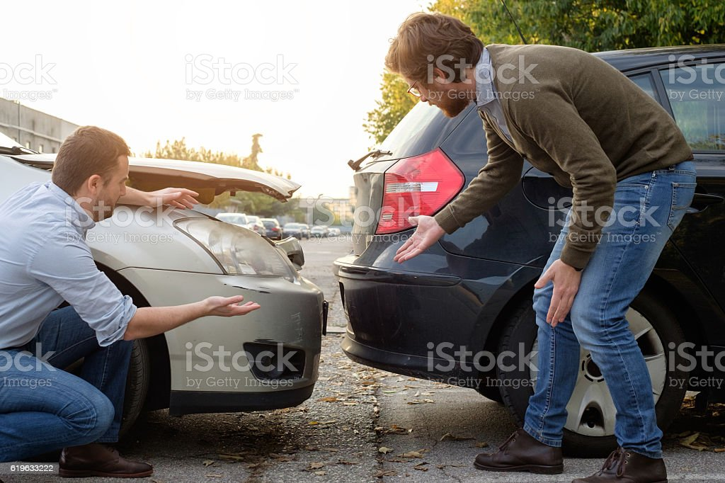 Two men arguing after a car accident on the road stock photo