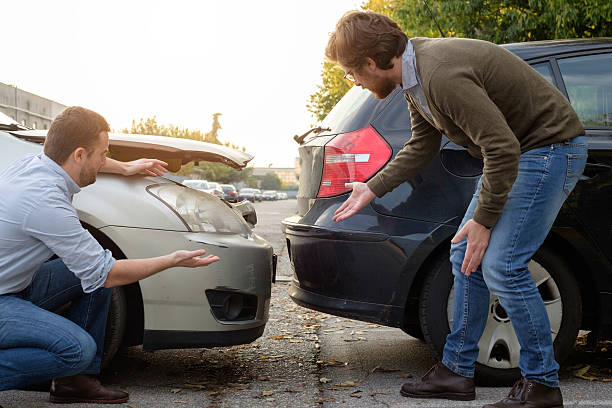 Two men arguing after a car accident on the road - foto de stock
