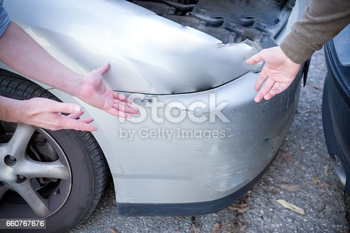 1047083324 istock photo Two men arguing after a car accident on the road 660767676