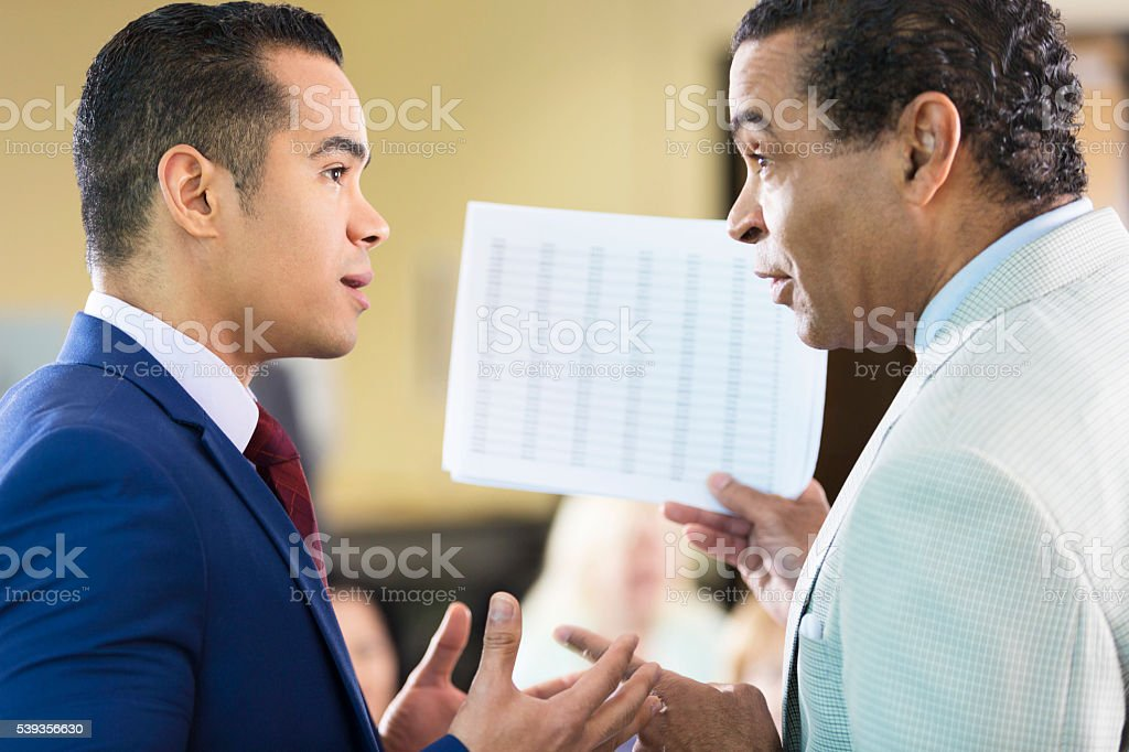 Two men arguing over paperwork stock photo