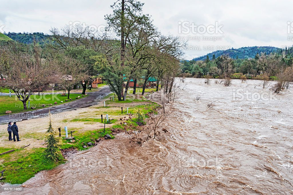 Two men at Coloma Campground watch American River High Waters stock photo