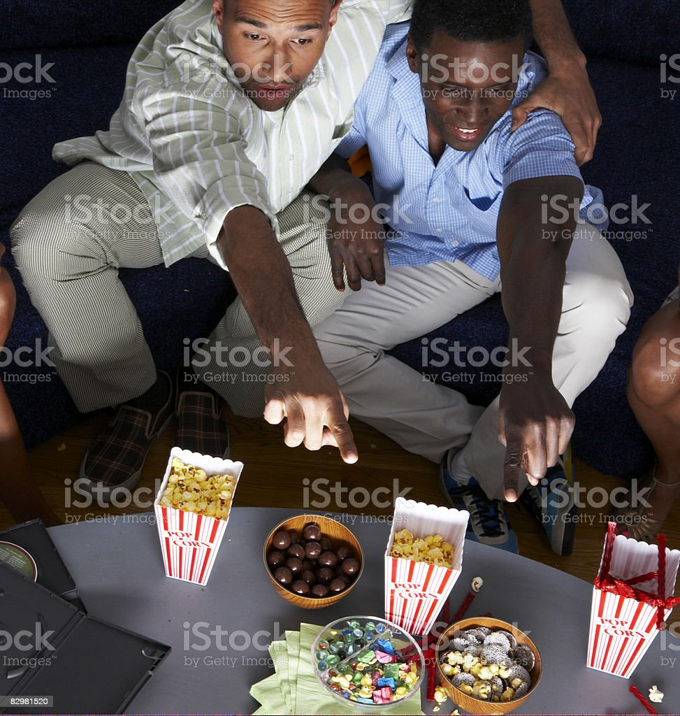 Two men at home watching television royaltyfri bildbanksbilder