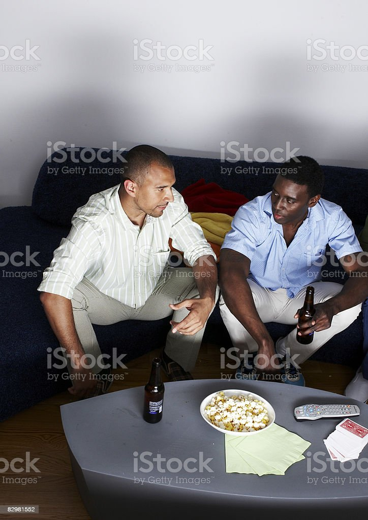 Two men at home watching television royalty free stockfoto