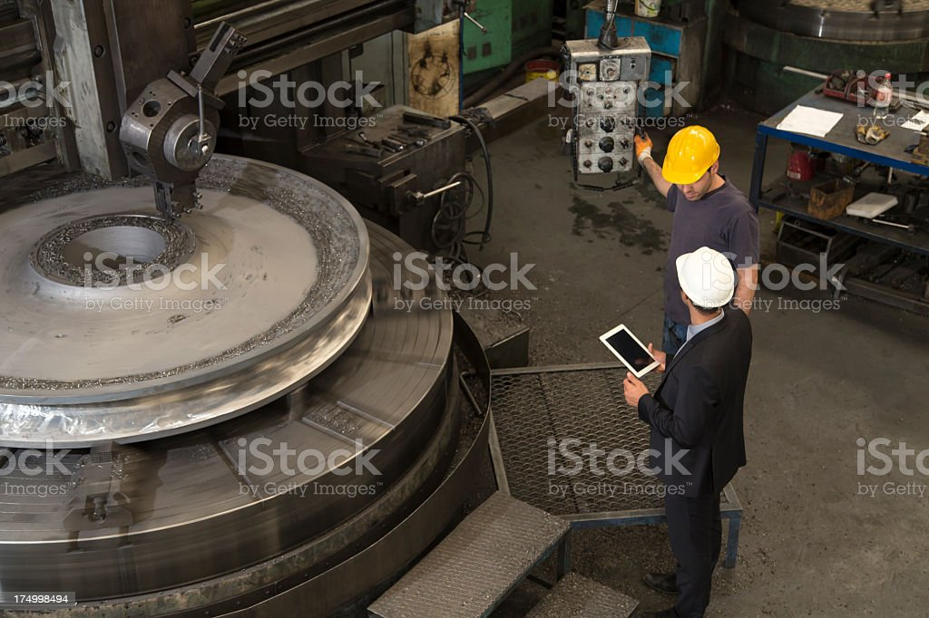 Two men at work in a factory wearing hard hats stock photo
