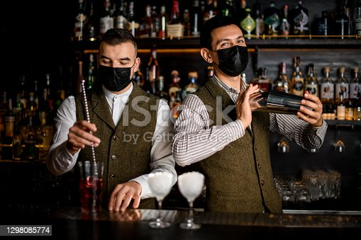 two men bartenders with masks on their faces preparing cocktails at the bar counter. Blurry glasses in the foreground
