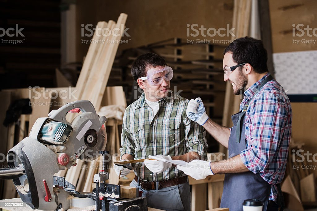 Two men builder with circular saw having a conversation stock photo