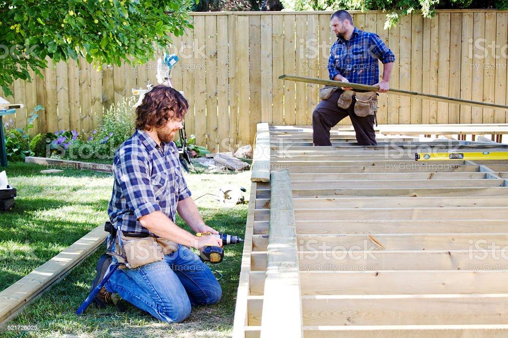 Two men building a deck stock photo
