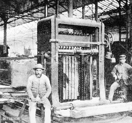 Two men by a Log Frame Sawing Machine. Heavy industry inside a train yard in Swindon from the pre-1900 book