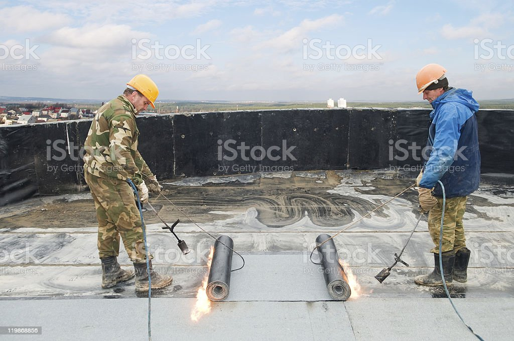 Two men carrying out roof covering works with roofing felt stock photo