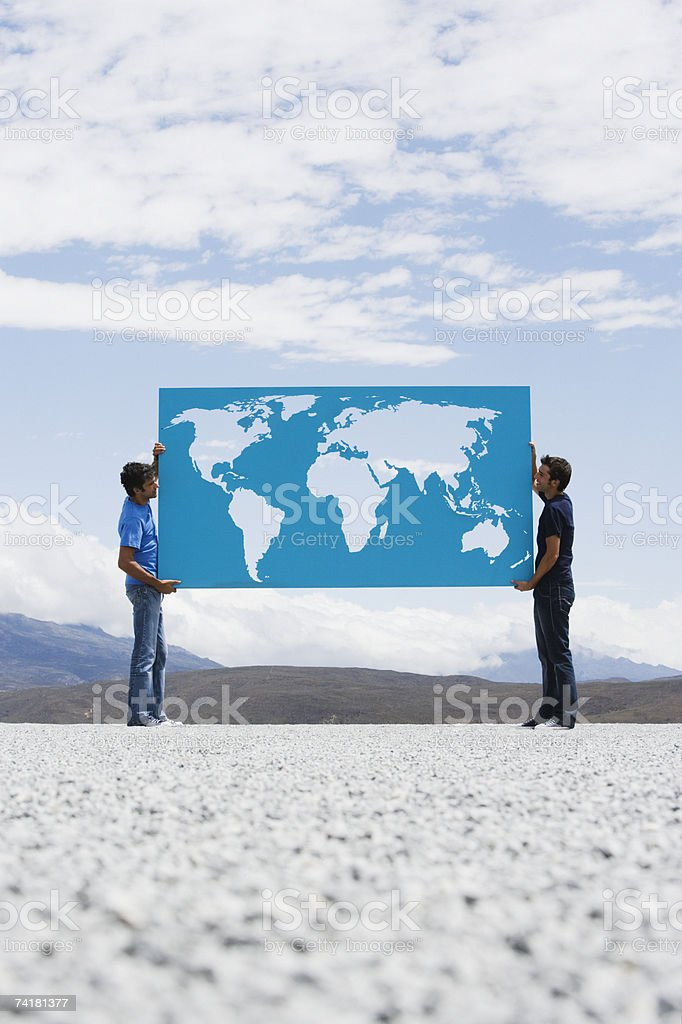 Two men carrying world map outdoors royalty-free stock photo