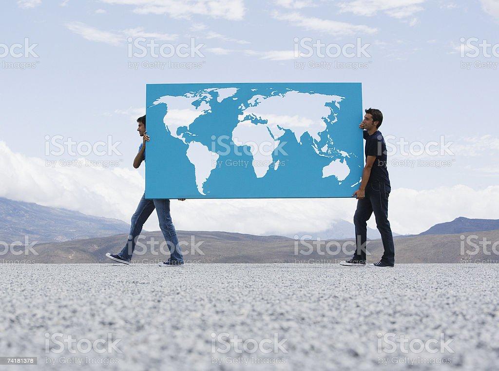 Dois homens carregar mapa do mundo ao ar livre foto de stock royalty-free