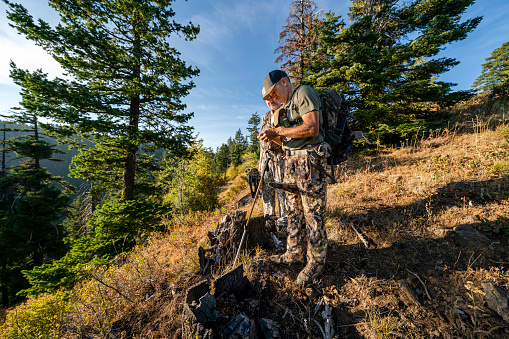 Two bowhunters tracking elk in a mountain range located in the Pacific Northwest region of the USA check their location using GPS on a mobile phone. One of the men is holding a bull elk grunt tube between his knees. The other man is holding a crossbow.