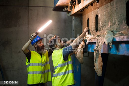two men check the state of the machinery in the basement of a structural and cement company