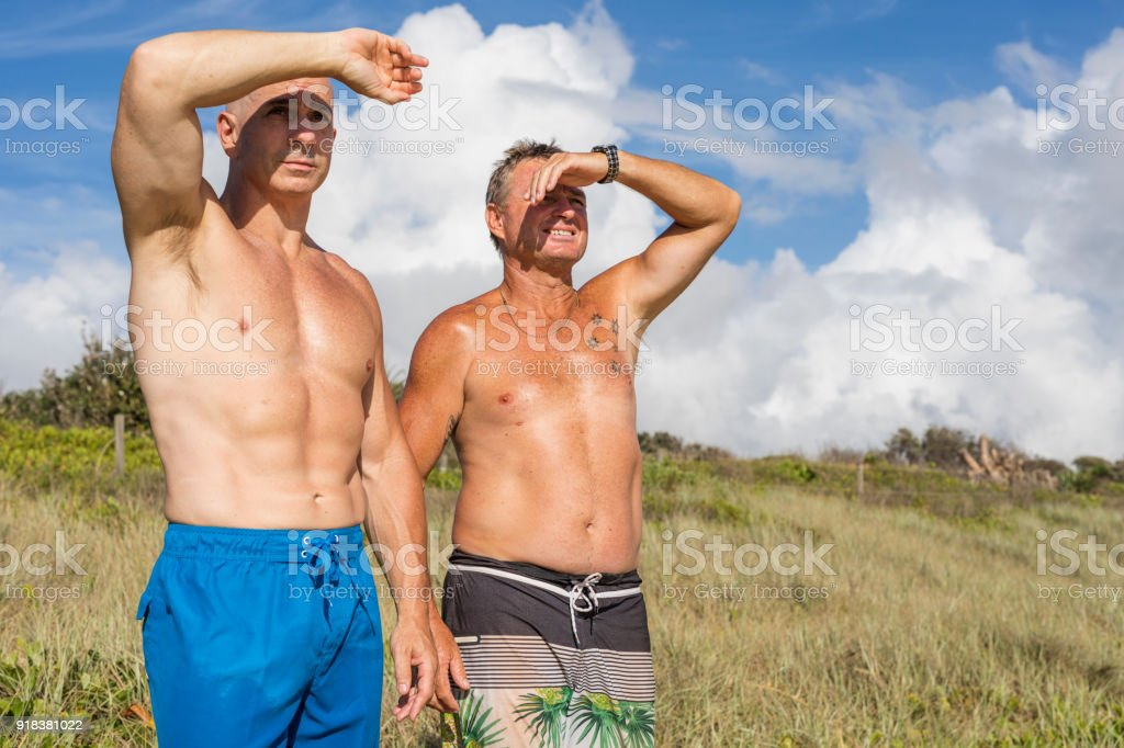Two Men Checking The Surf Conditions At The Beach Stock