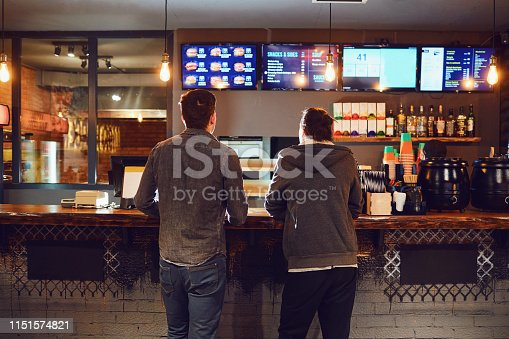 Rear view. Two men choose food in a fast food restaurant. Bar snack concept.