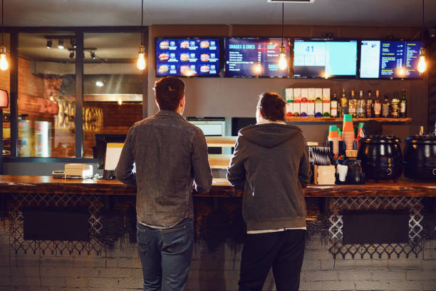 two men choose food in a fast food restaurant. - fast food restaurant stock pictures, royalty-free photos & images