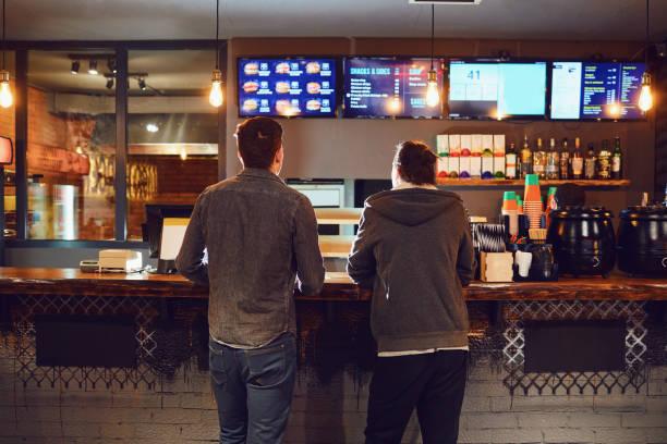 zwei männer entscheiden sich für das essen in einem fast-food-restaurant. - speisekarte stock-fotos und bilder