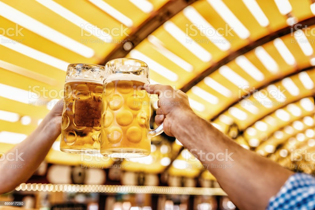 two men clinking beer glasses at oktoberfest in munich stock photo