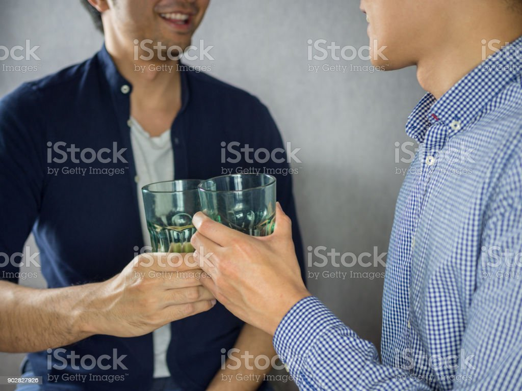 Two men clinking glasses and partying close up stock photo