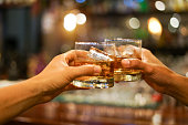 istock two men clinking glasses of whiskey drink alcohol beverage together at counter in the pub 1215644606
