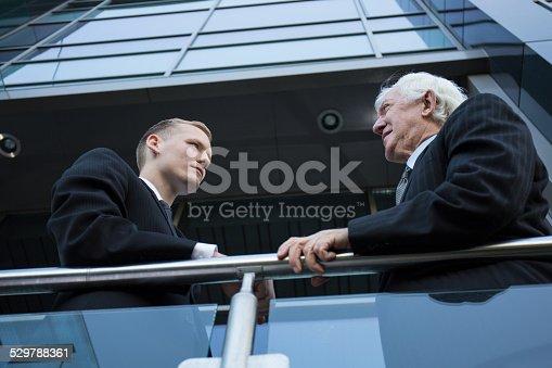 istock Two men conversing outside 529788361