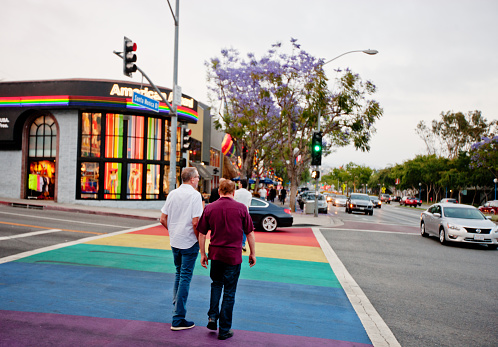 istock Two men crossing street colored as rainbow gay flag 471548341