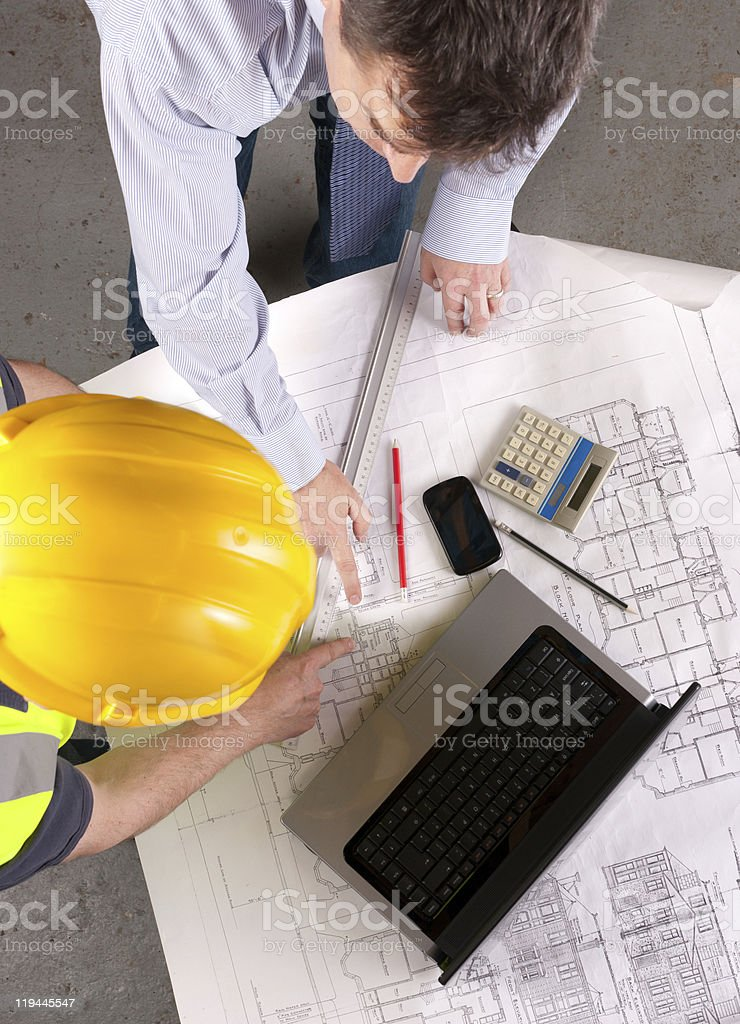 Two men discuss building plans royalty-free stock photo