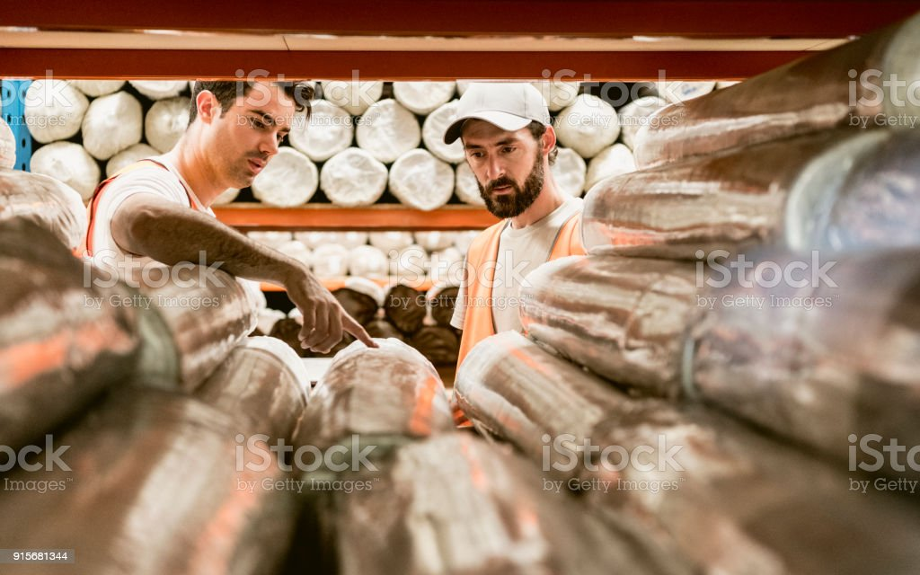 Two men discussing carpets in warehouse storage facility stock photo