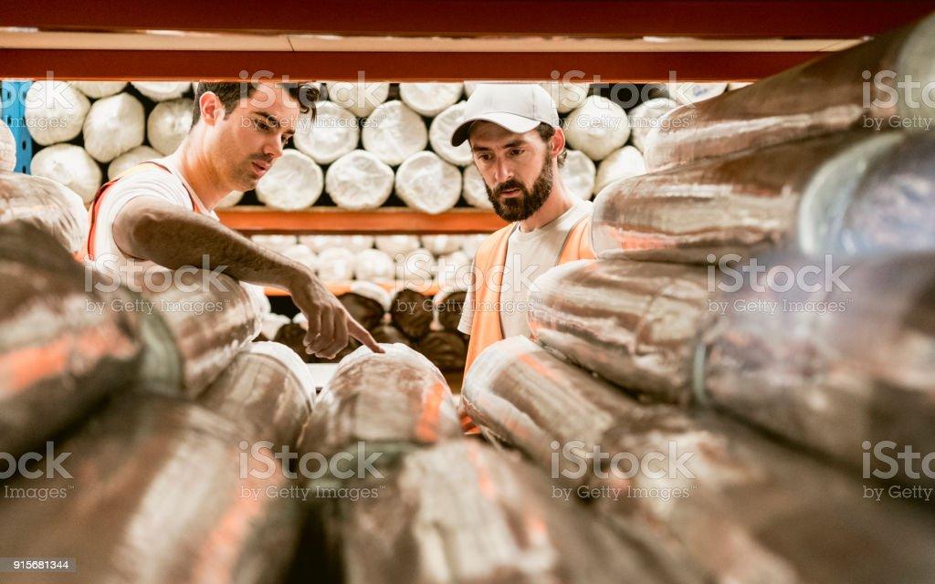 Zwei Männer diskutieren Teppiche im Lager Sammellager – Foto