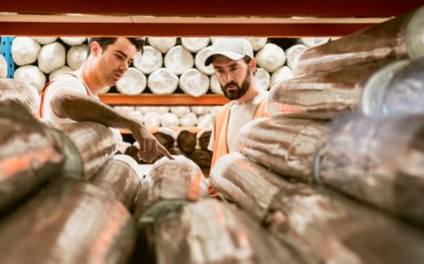 zwei männer diskutieren teppiche im lager sammellager - teppichmaterial stock-fotos und bilder
