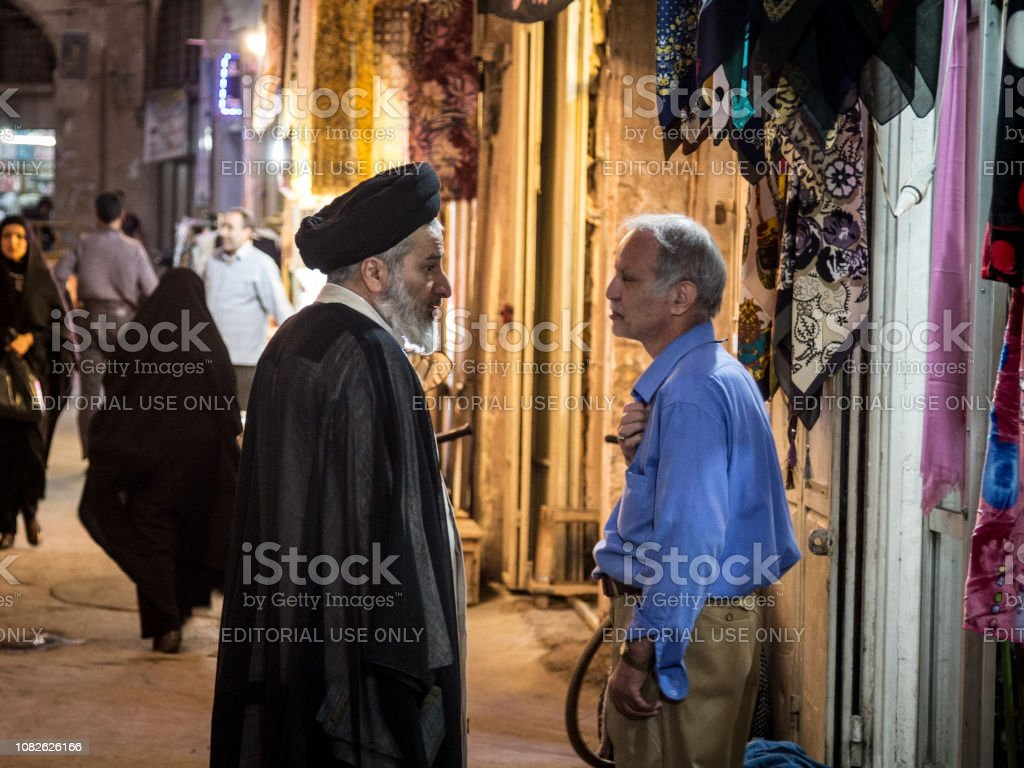 Two men discussing in Isfahan bazar, one wearing black turban, meaning he's a Sayyid, pr Syed, a descendent of prophet Muhammad according to shia islam stock photo