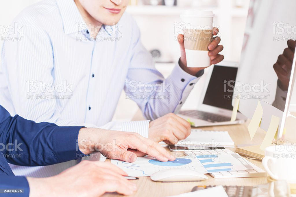 Two men discussing pie-chart stock photo