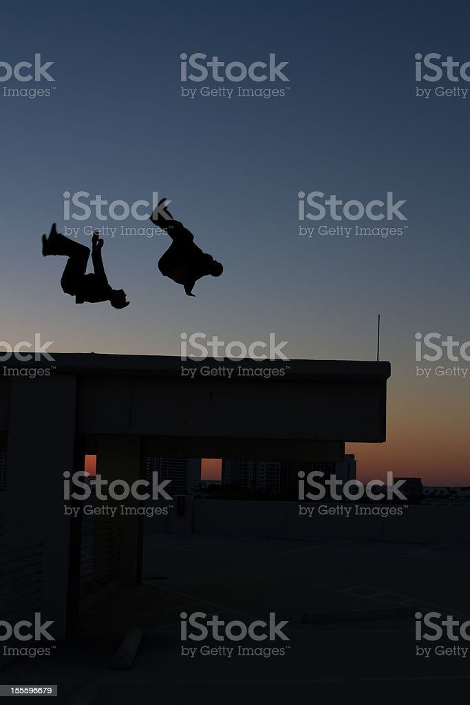 Two men doing flips on roof royalty-free stock photo