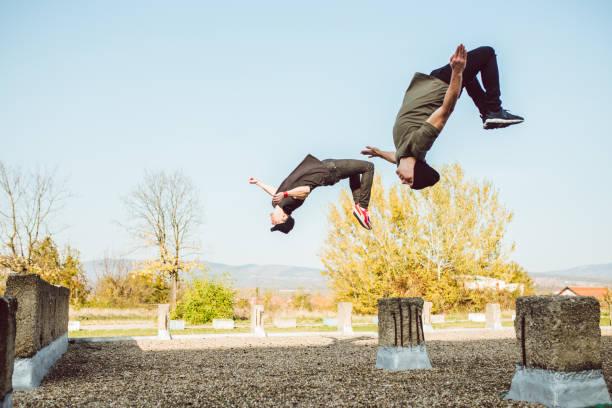 zwei männer, die frei laufenden parkour - parkour stock-fotos und bilder