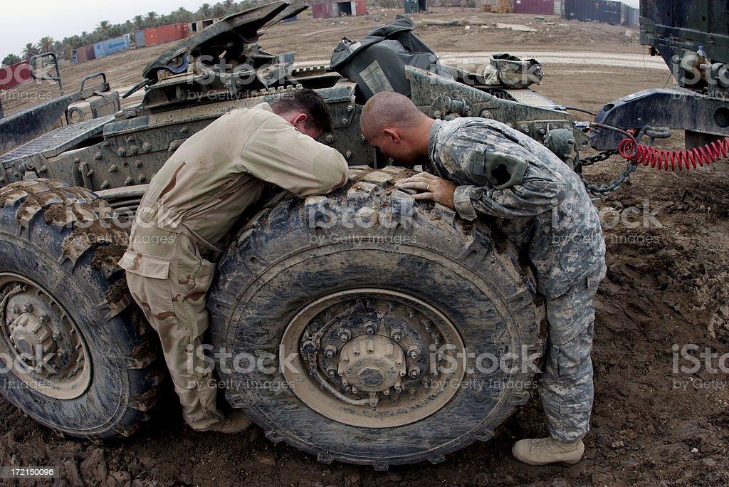 Two men doing maintenance on very large vehicle  stock photo