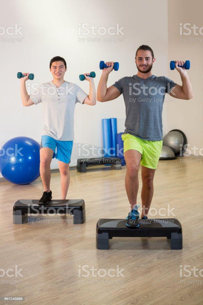 Zwei Männer Die Stepaerobicübungen Mit Hantel Auf Stepper