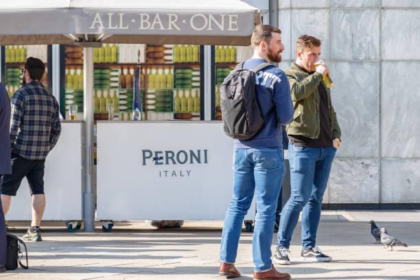 zwei männer trinken bier vor einer bar in canary wharf - mittagspause schild stock-fotos und bilder