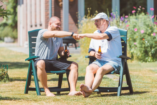 two men drinking beer together and making power five gesture in summer sunny garden (netherlands - holland) - male friendship and family party concept - older brother imagens e fotografias de stock