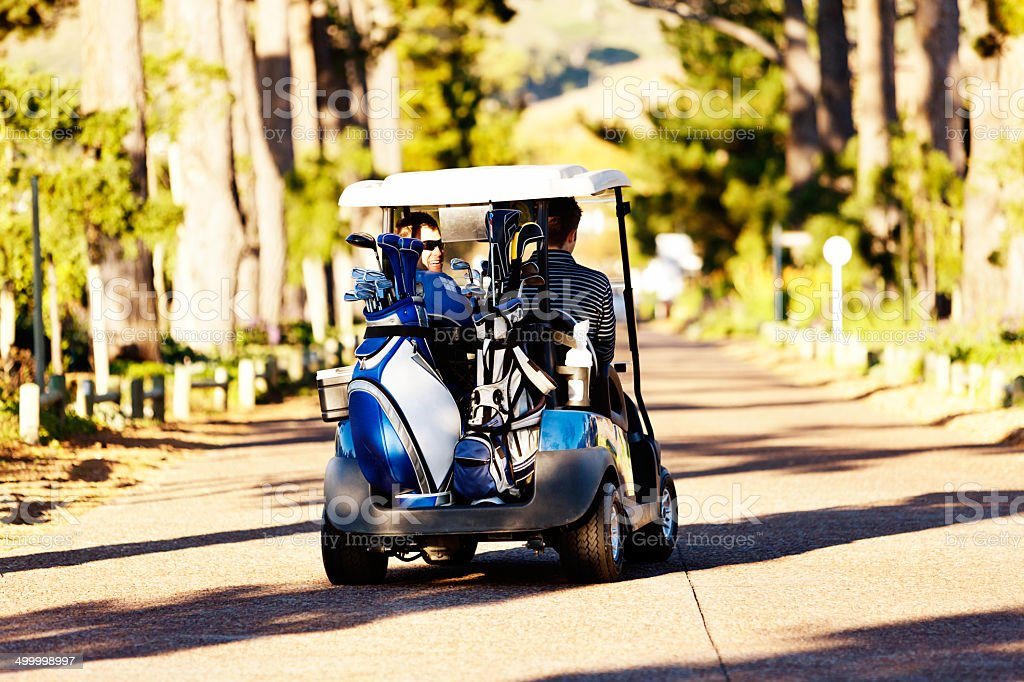 Two men driving electric golf cart along path stock photo