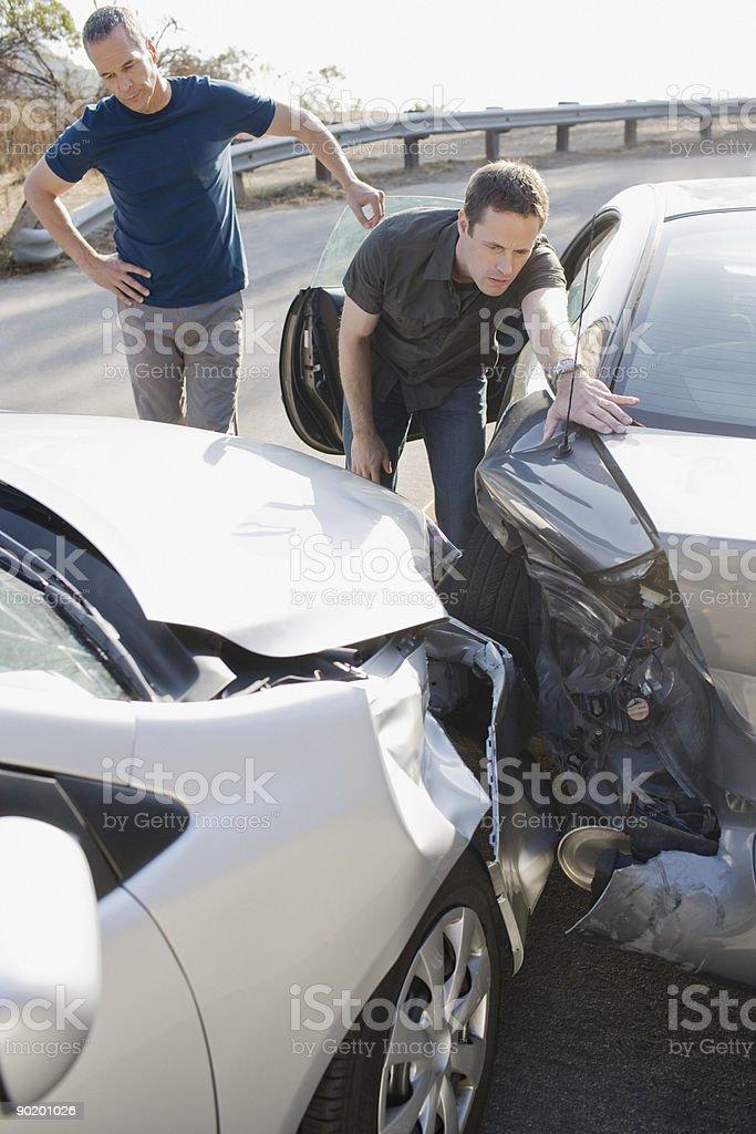 Two men examining damage in car collision stock photo