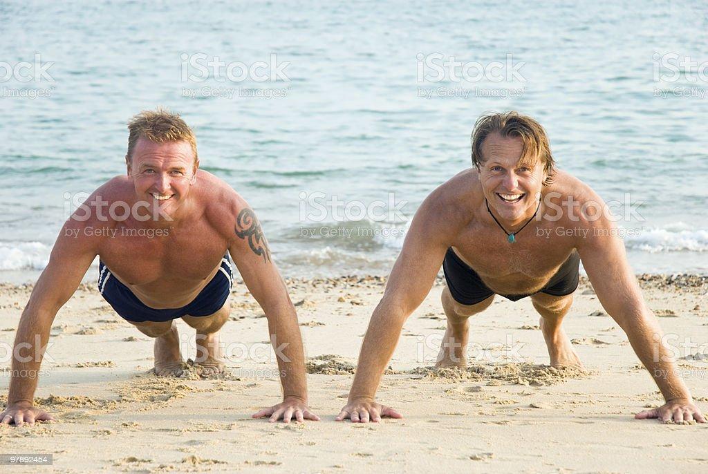 Two men exercising on beach. royalty-free stock photo