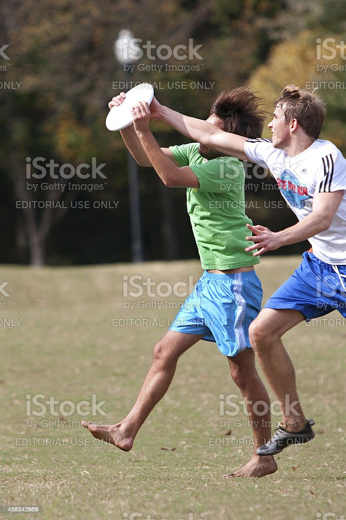 Two Men Fight To Catch Disc In Ultimate Frisbee Game royalty-free stock photo