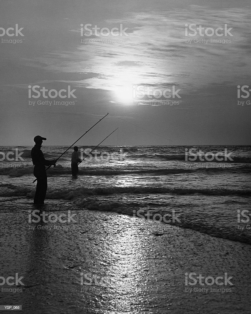 Two men fishing from shore at sunset royalty-free stock photo