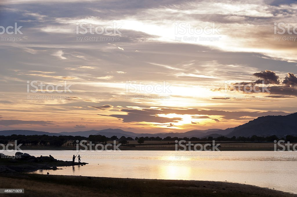 Two men fishing in the lake at sunset - 3 royalty-free stock photo