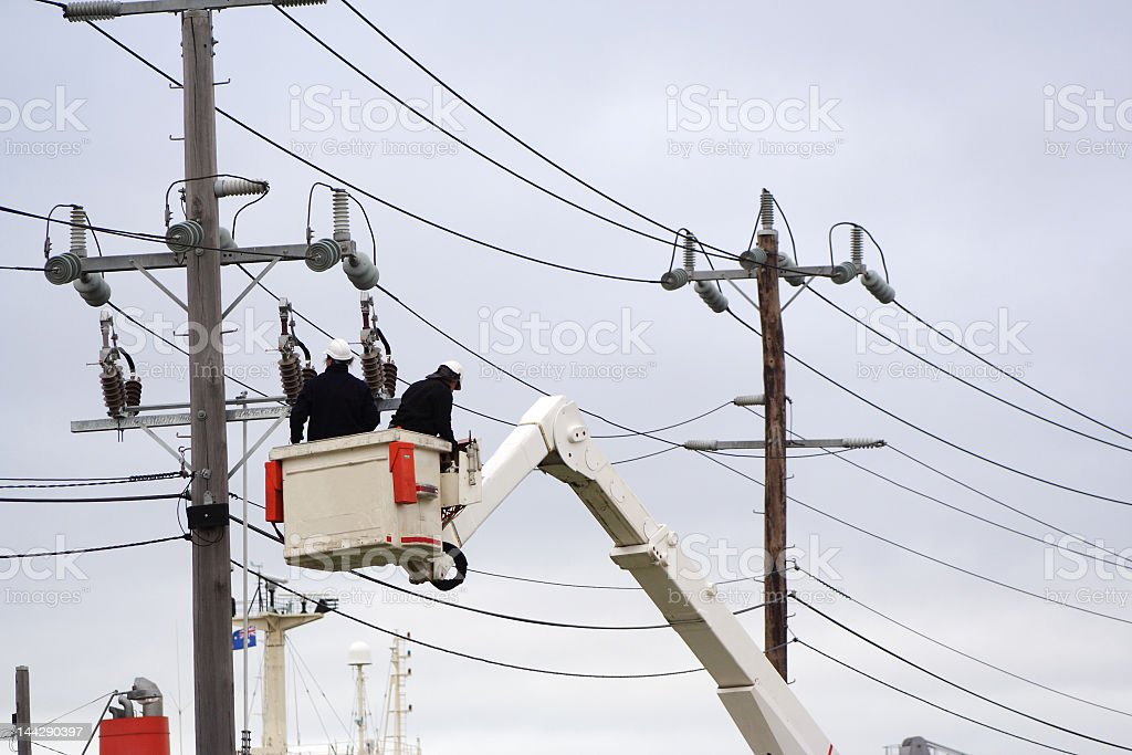 Two men fixing power lines on a cherry picker stock photo