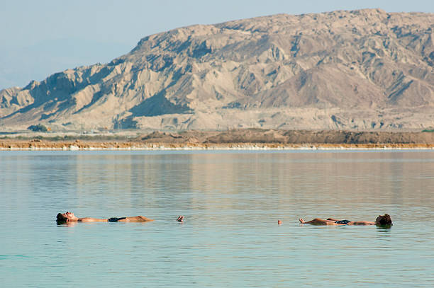 Two men Floating in the Dead Sea stock photo