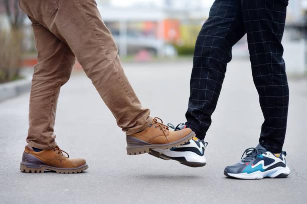 Two men greeting each other with foot instead of handshake. Friends or colleagues touch feet. Alternative non-contact greeting during coronavirus epidemic. Safety during COVID-19 or outbreak. stock photo