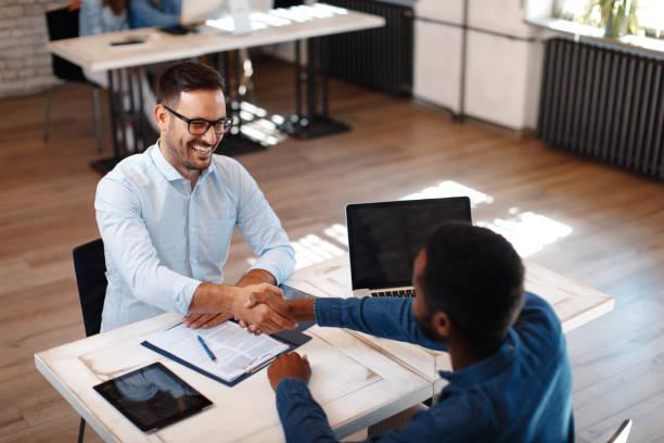 Two men handshake in the office stock photo