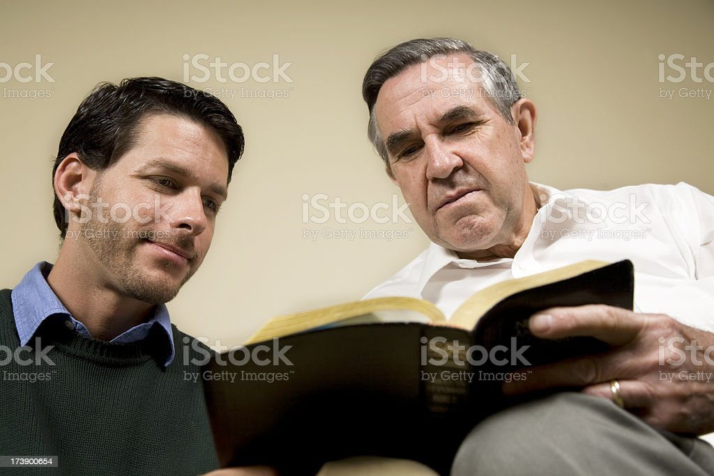 Two men happily studying the Bible together royalty-free stock photo